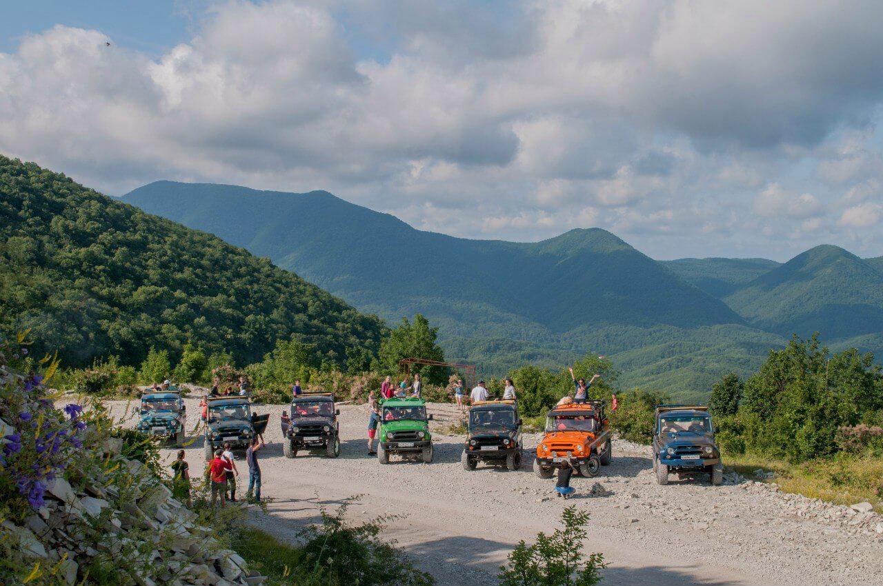 группа туристов на авто панорама гор