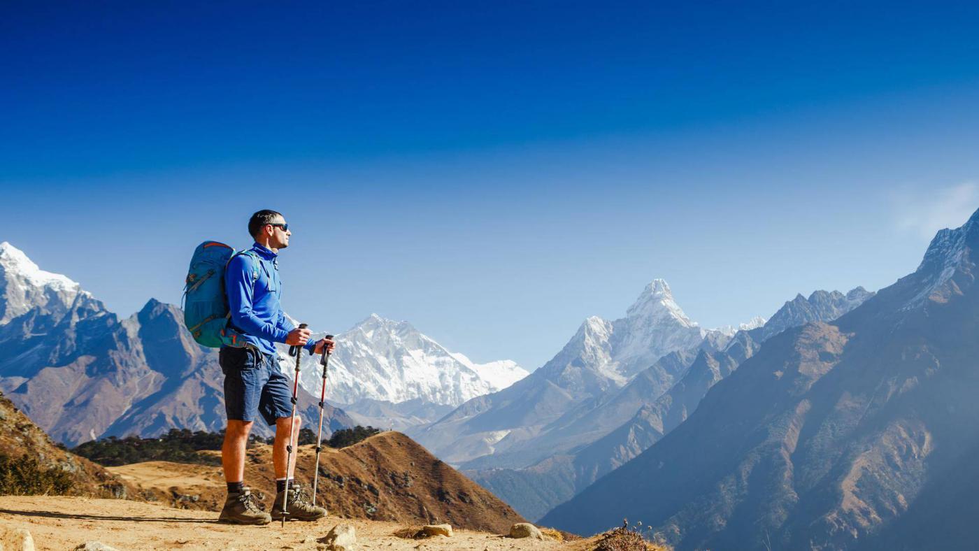 Турист с рюкзаком и палками для треккинга на фоне гор